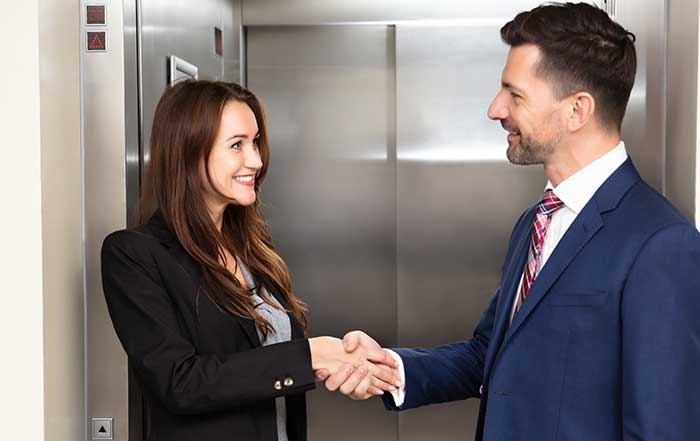 Two people shaking hands in front of elevator