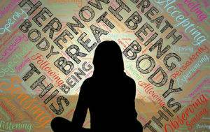 silhouette of meditating woman surrounded by words related to mindfulness