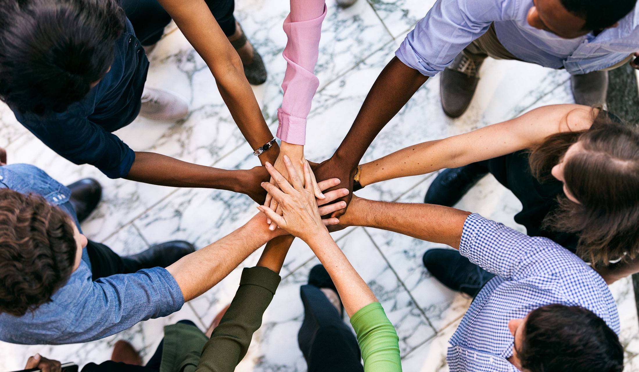 Team of coworkers of different races with hands together