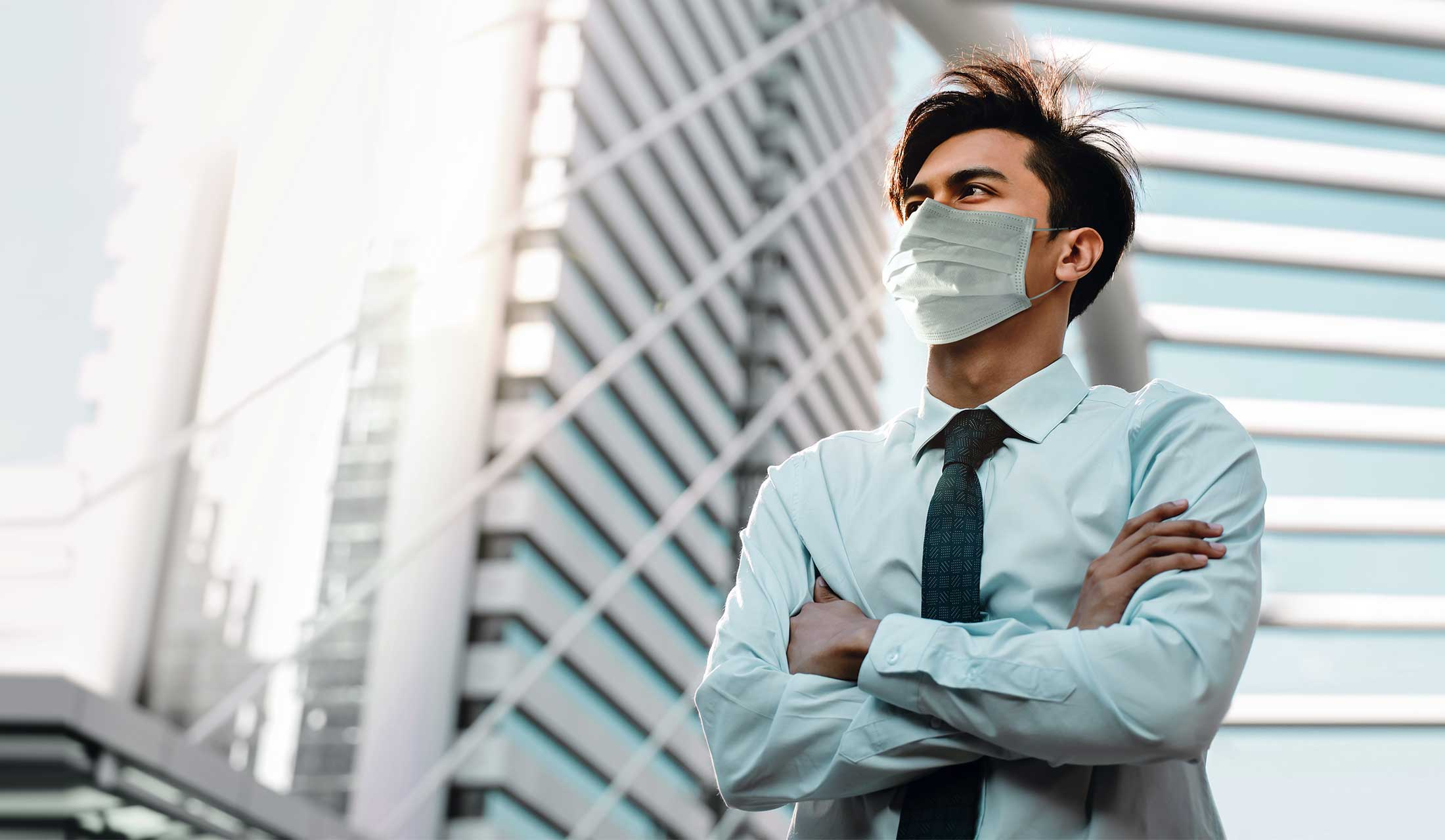 Business man wearing Covid mask looking reflective